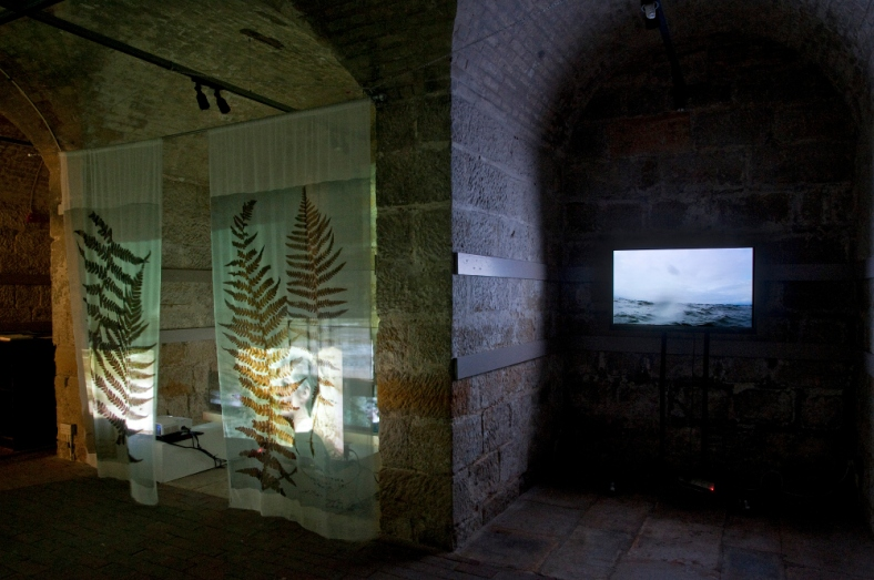 "on the right, next to the work of Jini Rowlins, my video ""You will always cherish the sea"" during the exhibition ""Ici et Là-Here and There"", in the ex-church of St. Mary in the Castle, Hastings (Uk)."